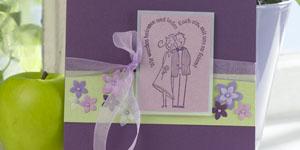 Ideen für die Hochzeit: Ein Herz und eine Seele | Einladung in Lila mit schönen Blüten und Brautpaar unter herzförmig geschwungenem Schriftzug