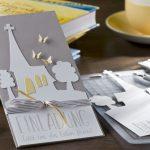 Ideen für Kommunion und Konfirmation: Komm zur Kirche | Einladung in Taupe und Weiß mit der Silhouette einer Kirche, zartgelben Schmetterlingen und einem geradlinigen Schriftzug