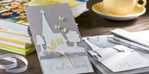 Ideen für Kommunion und Konfirmation: Komm zur Kirche | Einladung in Taupe und Weiß mit der Silhouette einer Kirche, zartgelben Schmetterlingen und einem schwungvollen Schriftzug