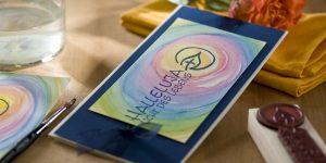 Ideen für die Kommunion und Konfirmation: Licht des Lebens | Einladungs- und Grußkarte in Dunkelblau und Weiß mit aquarelliertem Hintergrund in den Farben des Regenbogens