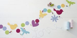 Ideen für den Frühling: Frühlingsliebe | Eine DIY Ideen für die Dekoration zuhause: Dekorative Kette aus selbst ausgeschnittenen Frühlingsboten und Perlen in kräftigen Frühlingsfarben.