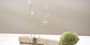 Ideen für Papierdraht: Frühblüher | Zarte Blüten aus Papierdraht in Grün und Weiß auf einem Stück Birke montiert