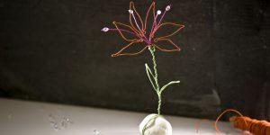 Ideen für Papierdraht: Funkelperlenblüte | Blüte aus Papierdraht in Orange, Pink und Grün mit Perlen und feinem Lichtspiel auf einem Stein montiert