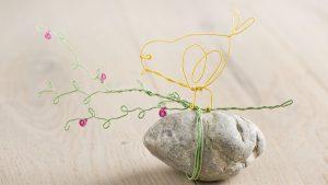 Ideen für Papierdraht: Blütenglück | Gelber Vogel, grüner Zweig und Blüten in Pink aus Papierdraht auf einem Kieselstein