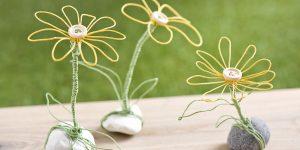 Ideen für Papierdraht: Dotterblumen | Blumen in Gelb mit einem Holzknopf als Blütenmitte auf einem Stein