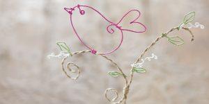 Ideen für Papierdraht: Vogelgezwitscher | Vogel aus Papierdraht in Pink auf Zweig mit grünen Blättern und weißen Blüten