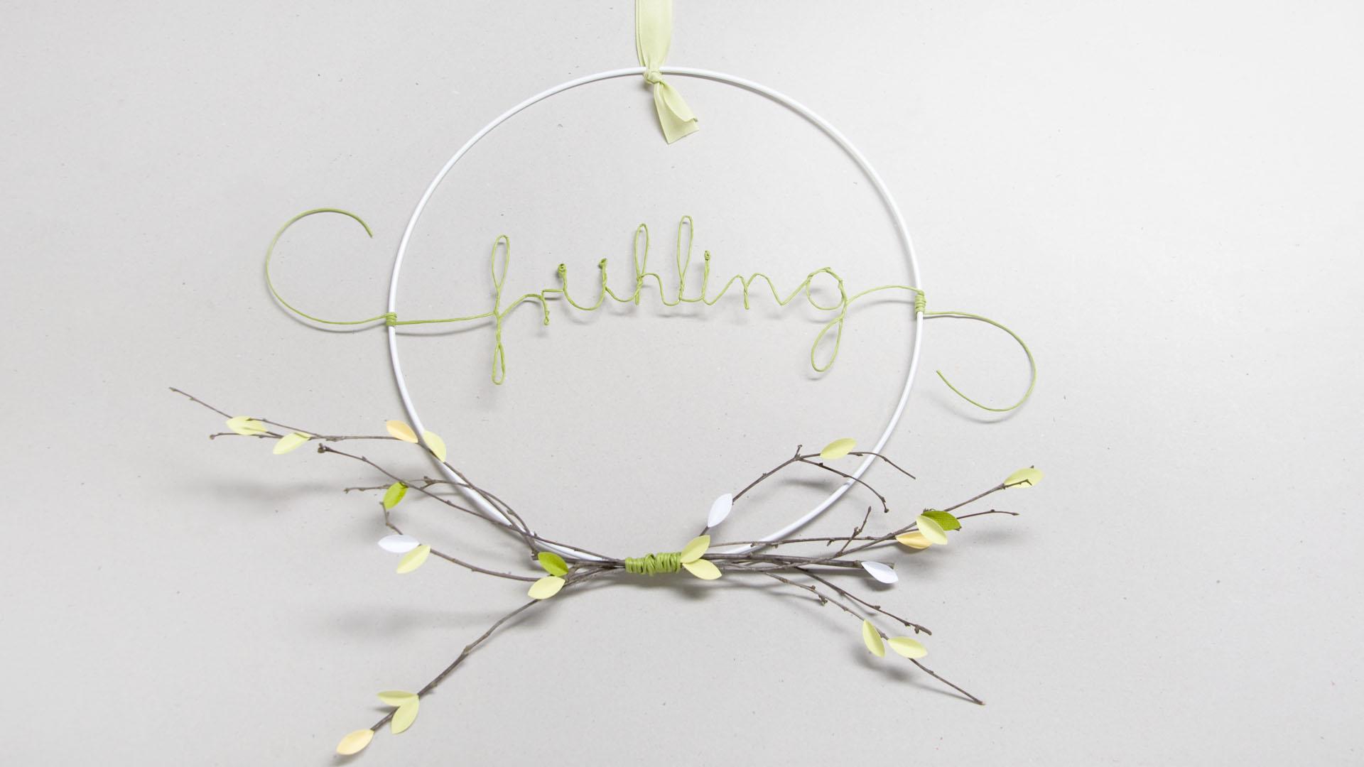 Ideen für den Frühling: Hula Hoop für die Deko zuhause | Metallring mit Papierdraht, Zweig und ausgestanzten Blättern in hellem Grün, Gelb und Weiß