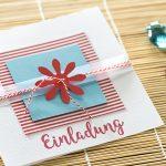 Ideen für besondere Geburtstage: Sommerbrise | Quadratische Einladungskarte in Weiß, Rot und Azur mit Blüte und gestempelten Schriftzug im Handlettering-Stil