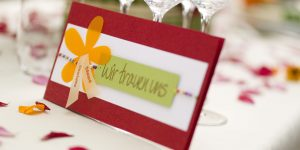 Ideen für Hochzeiten: Bunt wie das Leben | Einladung in Rot, Weiß, Orange und Grün mit Perlen, Blüte und Stempel für den Schriftzug