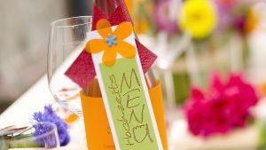 Ideen für Hochzeiten: Bunt wie das Leben | Hochzeitsmenü als Banderole mit Schriftzug und Blüte um eine Flasche Mineralwasser