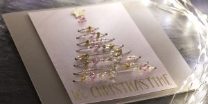 Ideen für die Weihnachtspost: Glanz und Gloria | Weihnachtskarte in Taupe, Rosé und Gold mit einem stilisierten Weihnachtsbaum aus aufgefädelten Perlen