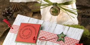 Ideen für die Weihnachtspost: Around the world | Weihnachtskarte und Windlicht mit Hüttenzauber: Holzkarton, rotes Karo, Naturbast, mehrsprachiger Schriftzug, Elch und Tannenbaum