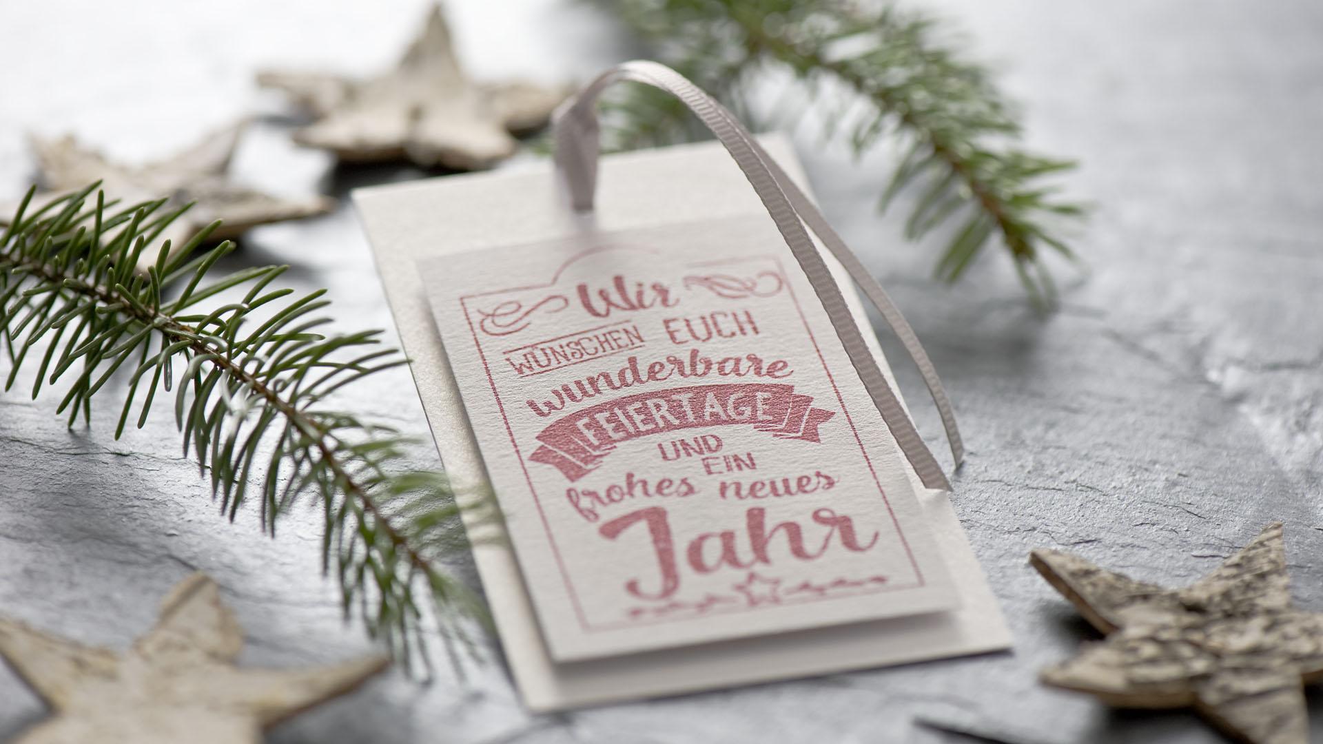 Ideen für die Weihnachtspost: Wir wünschen euch... | Schmucker Anhänger in Weiß, Grau und Rot mit Stempelmotiv im Handlettering-Stil