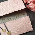 Ideen für Hochzeiten: Hand in Hand ein Leben lang | Einladung und Glückwunschkarte in Rosa, Grau und starkem Gold mit kalligrafiertem Schriftzug und Glitzer