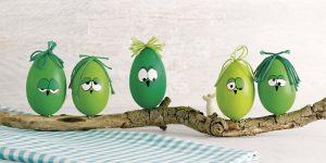 Ideen für den Frühling: Hei-ei-ei | Bemalte Eier mit lustigen Gesichtern und einem knorrigen Ast für ein witziges Dekostück in Grün